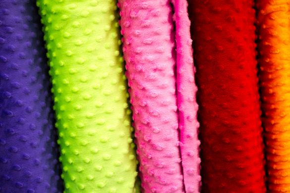 Bolts of vibrant plush dotted fabric (close-up). Colors include purple, lime green, pink, red, and orange.